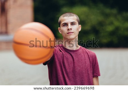 young male student holding basketball, serious face, horizontal - stock photo