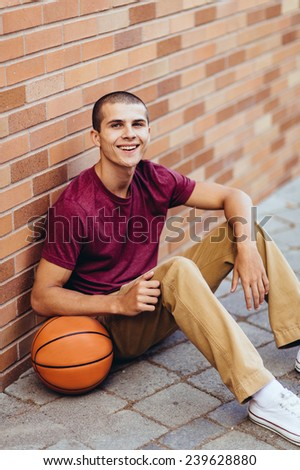 young male student holding basketball,sitting against brick wall, smiling - stock photo