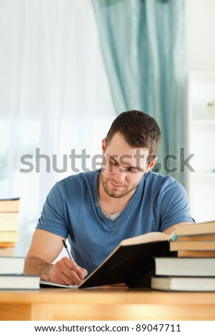 Young male student preparing book report