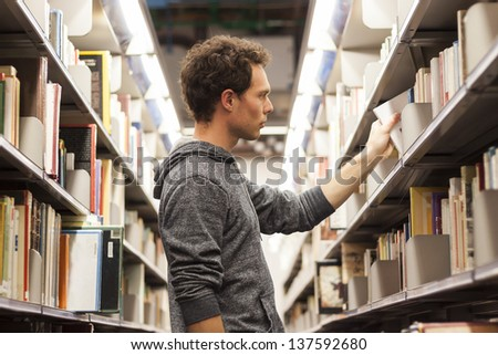 Young male student selecting a book from a library shelf, high school - stock photo
