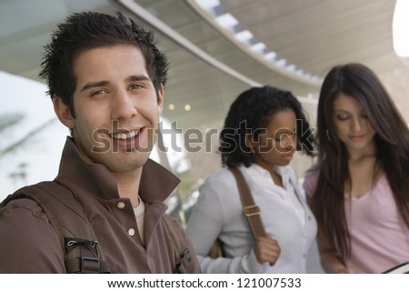 Young male student smiling standing in college corridor