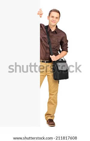 Young male student standing behind a panel isolated on white background