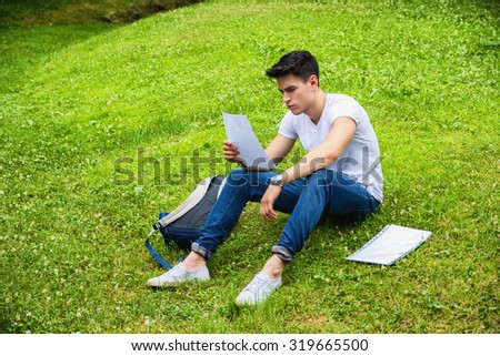 Young Male Student Studying his Lessons while Lying on Grass in City Park, Smiling at Camera - stock photo