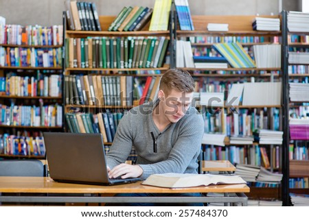 Young male student typing on laptop in the university library - stock photo