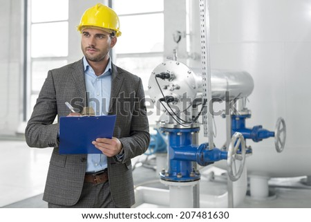 Young male supervisor writing on clipboard in industry - stock photo