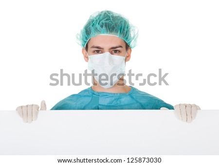 Young male surgeon in a cap and mask holding up a blank banner with copyspace for your text