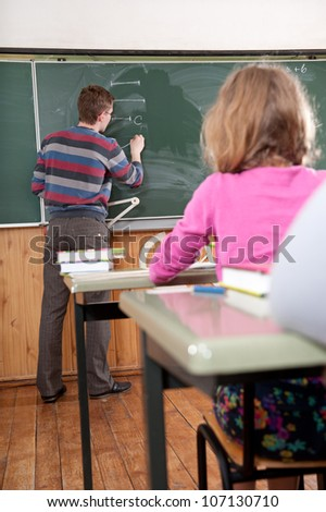 Young male teacher explaining math to the elementary age pupils at school