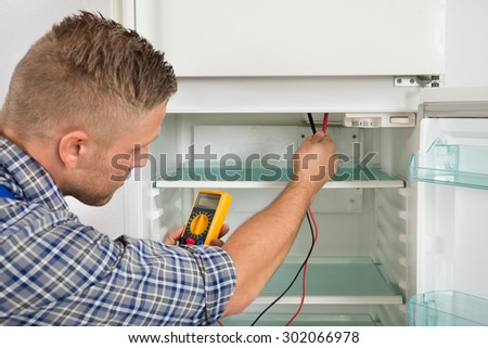 Young Male Technician Checking Fridge With Digital Multimeter - stock photo