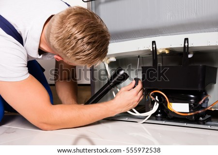 refrigerator repair. young male technician checking refrigerator with screwdriver repair