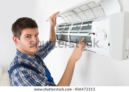 Young Male Technician Repairing Air Conditioner At Home
