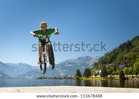 young male teenager jumps high with his dirt bike on a lake base - stock photo