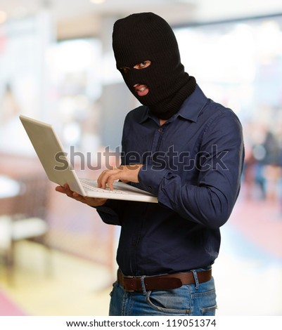 young male thief holding laptop, indoor