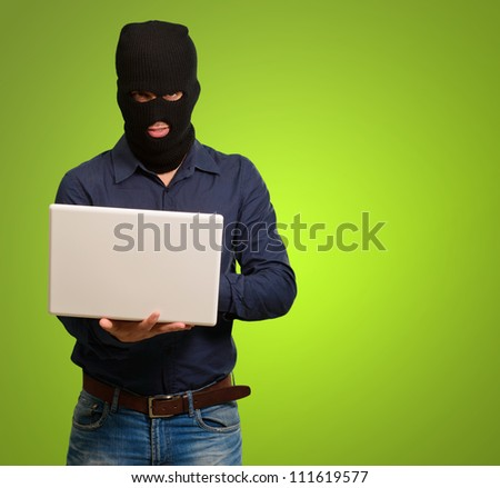 young male thief holding laptop isolated on green background