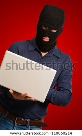 young male thief holding laptop isolated on red background - stock photo