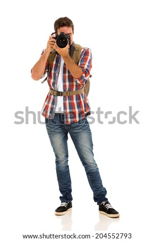 young male tourist taking photos isolated on white
