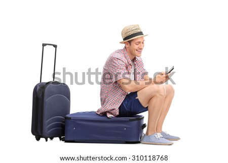 Young male tourist typing a text message on his cell phone an sitting on his luggage isolated on white background - stock photo