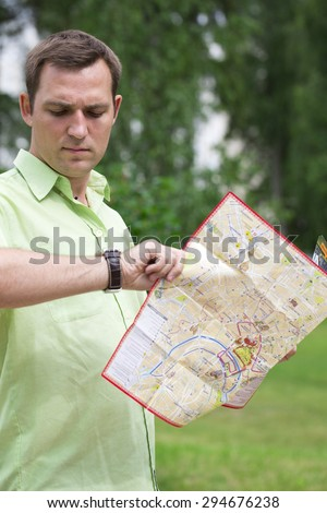Young male tourist with map in hand looking at wristwatch. Tourist map of the city of Moscow, Russia (no trademark) - stock photo
