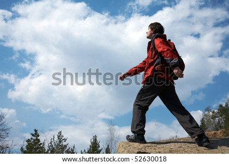young male traveler is walking through the mountains on the background of the beautiful sky