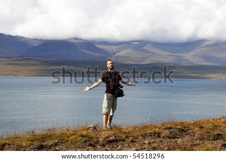 Young male traveler, photographer enjoying the beautiful view of mountains and ocean in Iceland - stock photo
