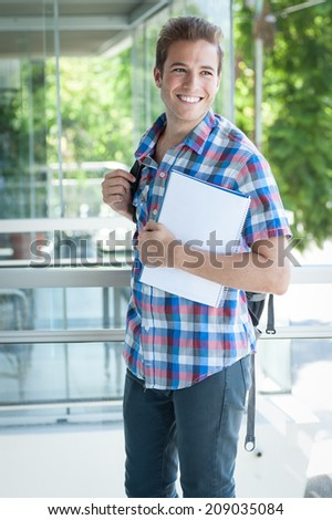 Young male wearing backpack and holding folder - stock photo
