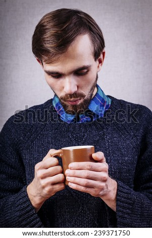 Young male with beard, blowing  in cup of tea - stock photo