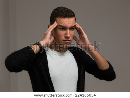 Young male with headache on grey background. Studio shot - stock photo