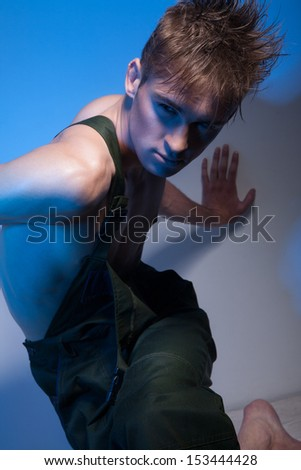 Young male with muscular torso, attractive face and fashionable hairstyle, dressed in dark green coveralls, with his hand on the wall looking away - stock photo