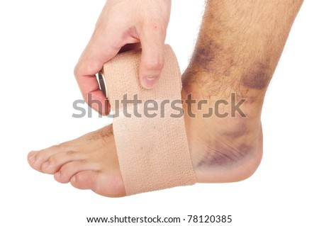 young male with sprained ankle applying medical bandage (isolated on white background) - stock photo