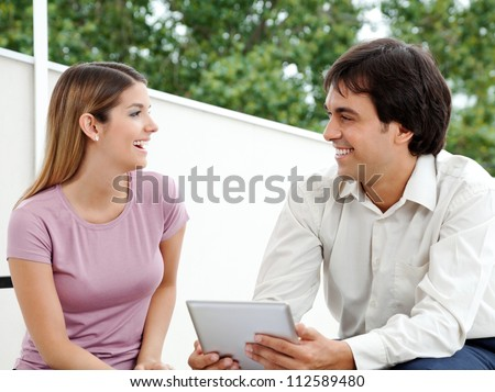 Young male with tablet PC smiling while looking at female