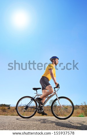 Young male with yellow shirt and helmet riding a mountain bike outdoors on a sunny day, shot with a tilt and shift lens - stock photo