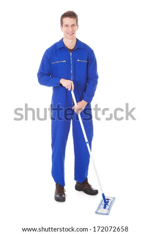 Young Male Worker In Boilersuit Cleaning Floor With Mop