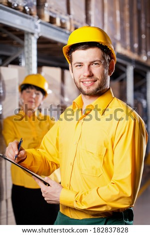 Young male worker in yellow uniform in warehouse