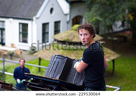 Young male worker posing while roofing a house near the city of Breda, Netherlands, Europe, in a traditional craftsman way - stock photo