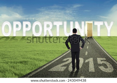 Young male worker standing on the road while looking at an opened opportunity door with number 2015 - stock photo