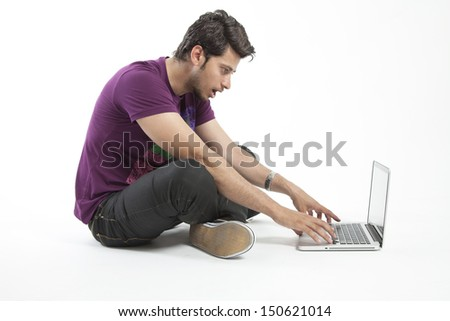 Young male working on a laptop with shocked expression - stock photo