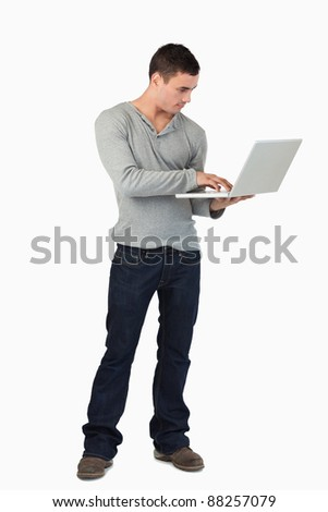 Young male working on laptop against a white background