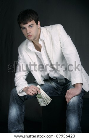 Young man, a businessman in a white jacket and jeans
