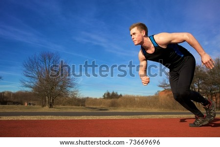 Young man accelerating in to spring on sports track - stock photo