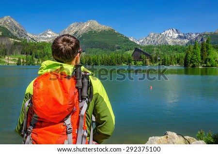 Young man admires the view of high mountains and mountain lake in National Park High Tatra, Slovakia, Europe