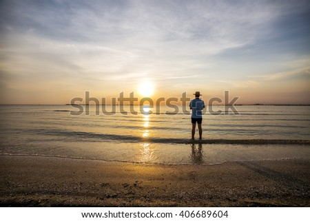 Young man admiring the spectacular sunset above the sea - stock photo