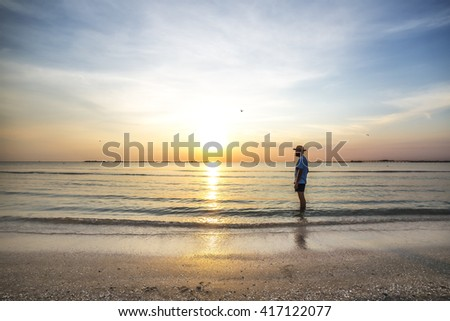 Young man admiring the spectacular sunset above the sea