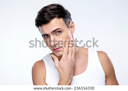 Young man after shaving over gray background - stock photo