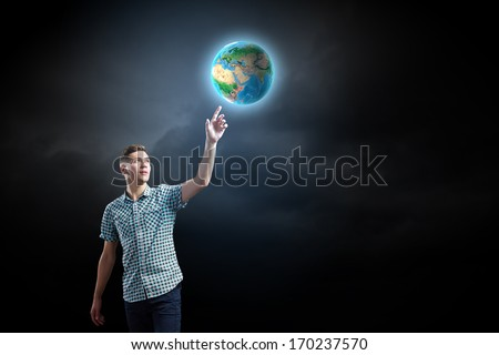 Young man against dark background and Earth planet image. Elements of this image are furnished by NASA
