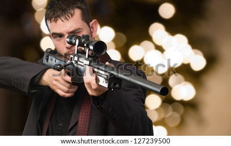 Young Man Aiming With Rifle against an abstract background