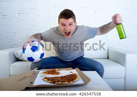 young man alone holding ball and beer bottle watching football game on television sitting at home living room sofa couch with pizza box celebrating goal or victory gesturing crazy - stock photo