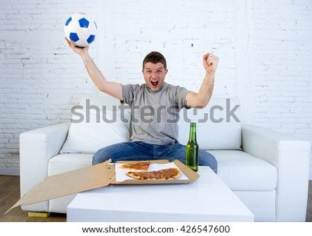 young man alone holding ball watching football game on television sitting at home living room sofa couch with pizza box and beer bottle celebrating goal or victory gesturing crazy - stock photo
