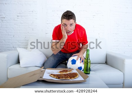 young man alone holding ball with beer and pizza in stress wearing team jersey watching football game on television at home living room sofa couch excited in disbelief face expression - stock photo