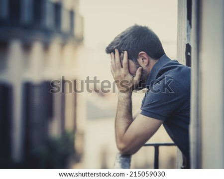 young man alone outside at house balcony terrace looking depressed, destroyed, wasted and sad suffering emotional crisis and depression on urban background  - stock photo