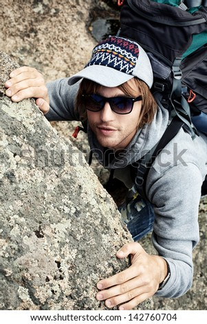 Young man alpinist is climbing on a mountain.