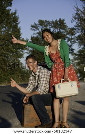 Young man and asian girl with a big smile have their thumbs out to hitch a ride along the roadside. They are traveling with their suit cases. - stock photo